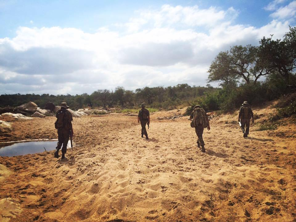 four rangers walking through sand