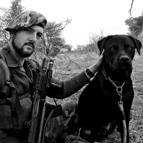 a ranger kneeling down with a gun and a black lab