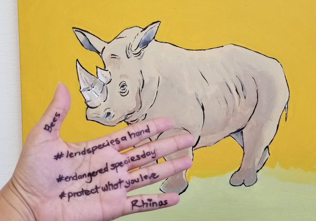 A hand in front of a rhino painting with #lendspeciesahand, #endangeredspeciesday, #protectwhatyoulove, bees, and rhinos written on it in black marker.