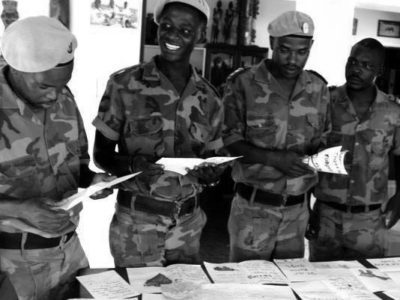 Four rangers in camouflage standing around a table reading letters