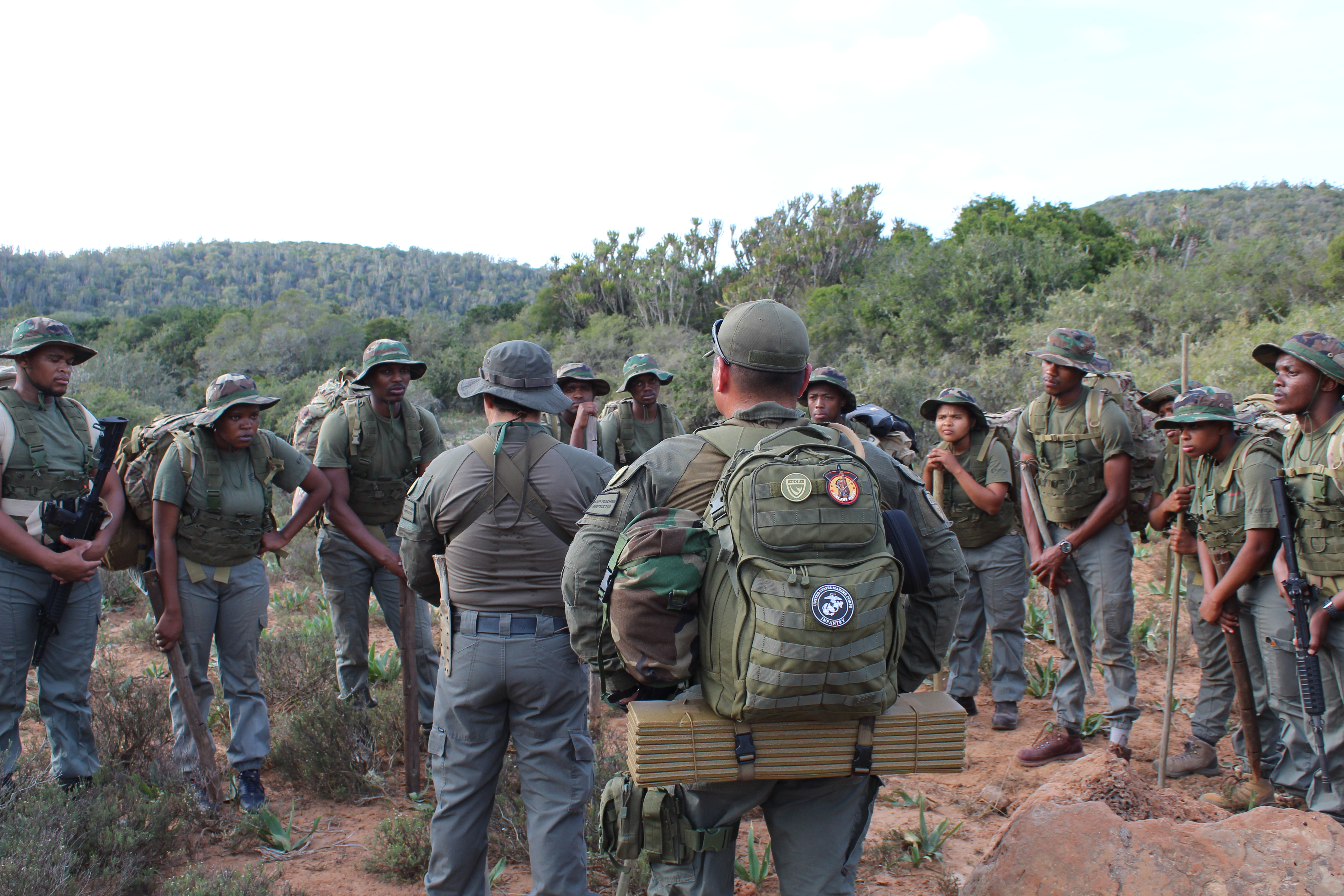 Men and women dressed in olive green standing outdoors in the bush listening to their instructor