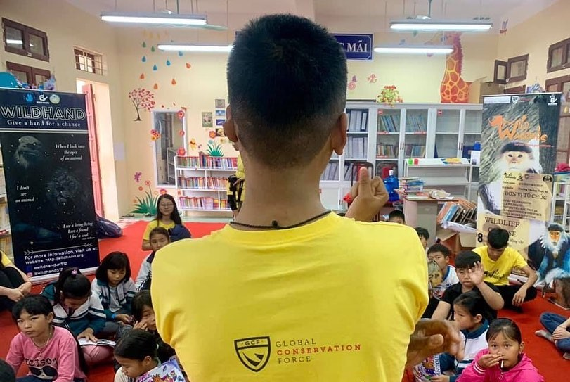 a man wearing a yellow shirt stands with his back to the camera in front of an elementary school classroom