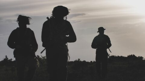 3 rangers silhouetted against a grey dawn sky