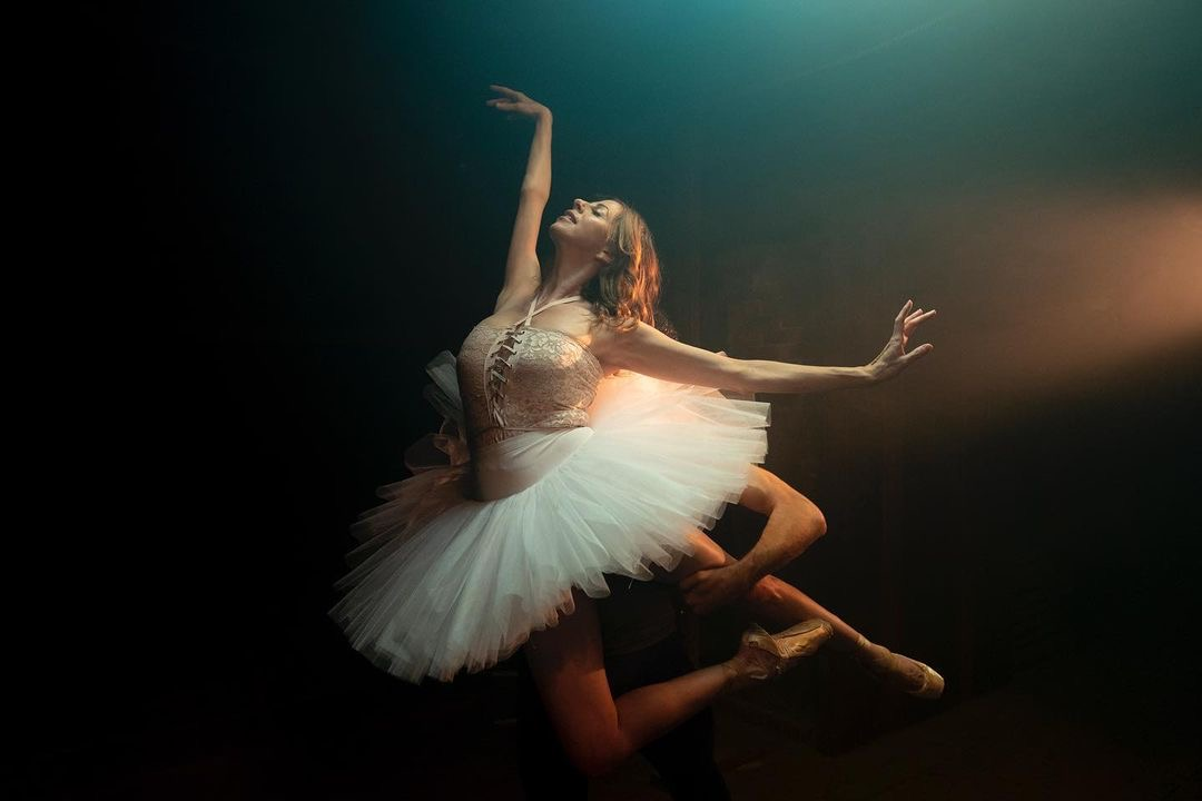 A ballerina in a white tutu is lifted off the ground.